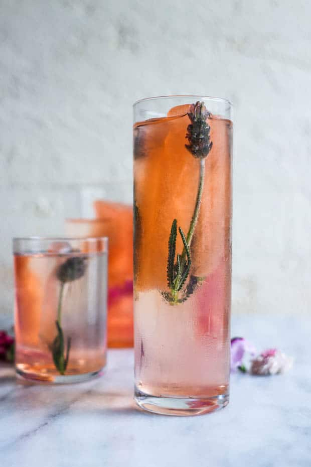 3 glass filled with long pink hued ice cubes that have lavender buds frozen in them, sit on a marble table top. There are edible flowers scattered on the table around the glasses.