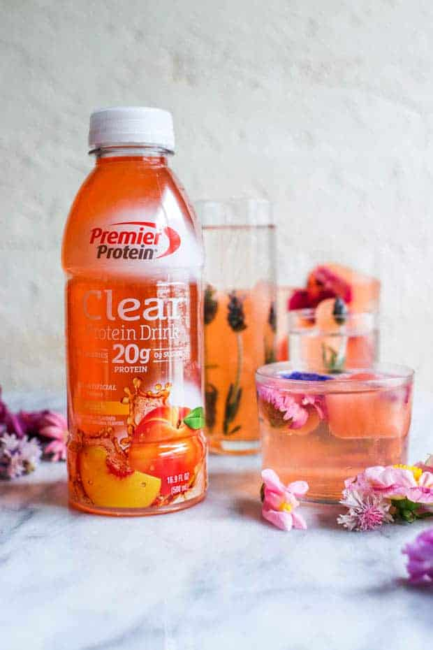 3 glass of varying heights filled with pink hued blooming  edible flower ice cubes and filtered water. There is also a bottle of Premier Protein Clear Peach Protein Drink next to the glasses and edible flowers are scattered across the table top.