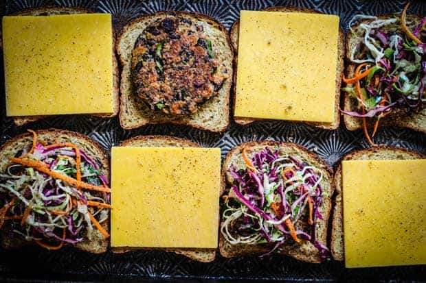8 slices of bread on a baking sheet some are topped with slices of cheddar, some with veggie burger patties and some have the patties topped with a colorful slaw.