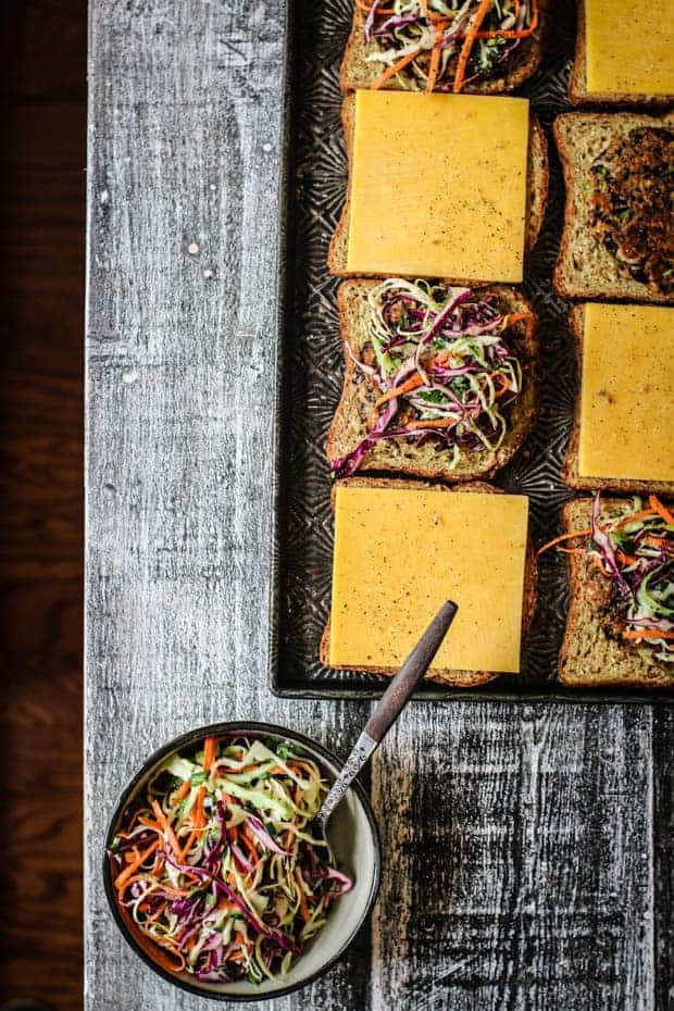 A sheet pan of prepped oats melts o a table next to a bowl of slaw.