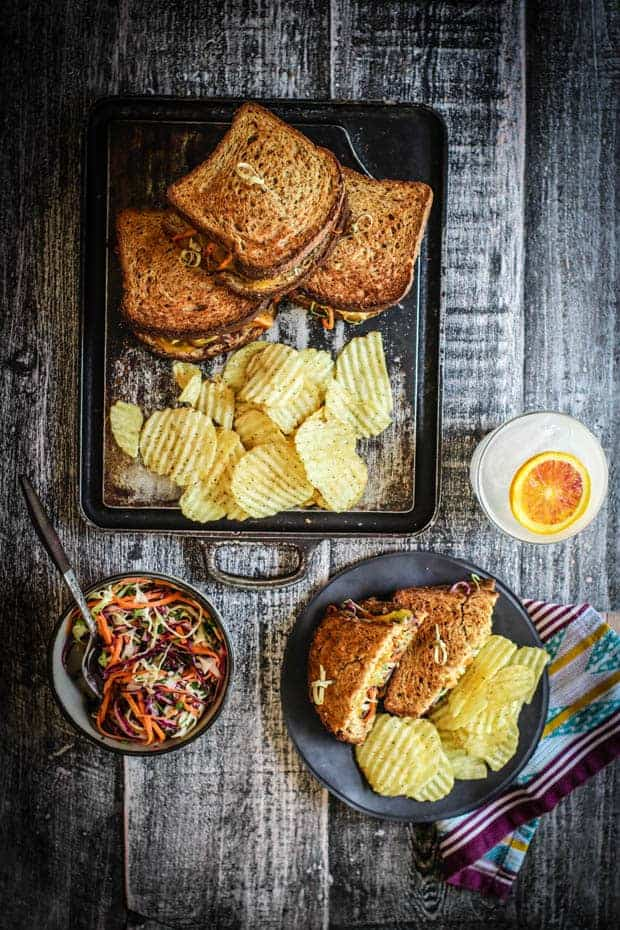 A plate with a colorful vegetarian patty melt ad chips sits on a table next to a serving platter piled high with more patty melts and chips. There is a bowl of slaw on the table and a glass filled with water and citrus slices.