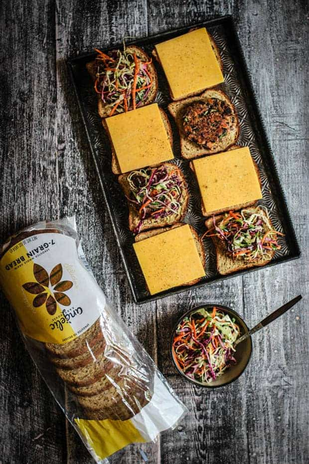 Sheet pan with 8 slices of bread some topped with slices of cheddar cheese, some with veggie burger patties and slaw, sits on a table next to a bag of Angelic Bakehouse bread and a bowl of colorful salsa