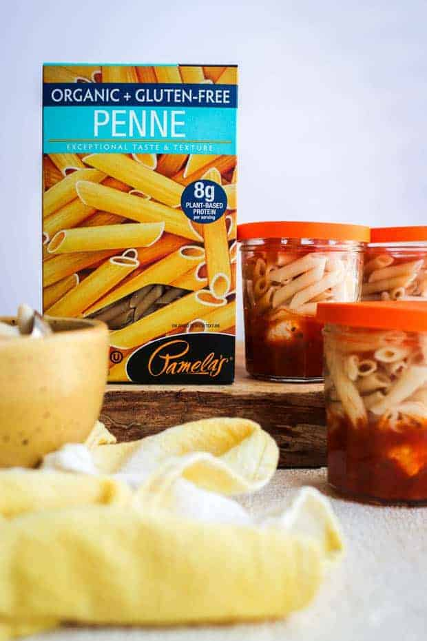 A box of Pamela's gluten free penne pasta on a wooden board next to small glass jars that are layered with marinara sauce, mozzarella balls, and gluten free pasta.