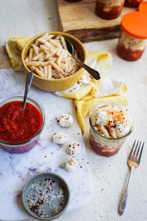 A prep scene where small glass jars are being filled with pasta sauce, mozzarella balls, and pasta.