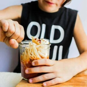 """A little boy in a sleeveless black t-shirt that says """"Old Soul"""" is sitting at table. He is using a fork to dig into a small jar that is layered with pasta sauce, mozzarella balls, and gluten free pasta"""