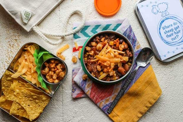 A lunchbox scene. There is a round stainless steel dish filled with taco soup. There is a small bento box next to that with tortilla chips, shredded cheese, and corn nuts for topping.