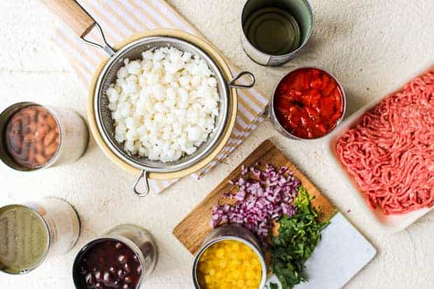 A variety of open canned goods, ground beef, and a cutting board with red onion pieces and minced cilantro all sit on a table top together. It is all of the ingredients for making taco soup together in one prep shot.