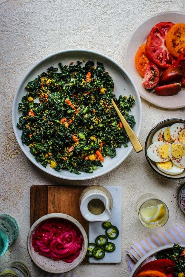 A big bowl of kale and quinoa salad with shredded carrots and chickpeas is on a table next to a plate of sliced heirloom tomatoes, a bowl of hard boiled egg halves that have been seasoned with red pepper flakes, a bolwl of pink marinated onions, slices of green jalapeño are scattered on the table and there is a small carafe of dressing.