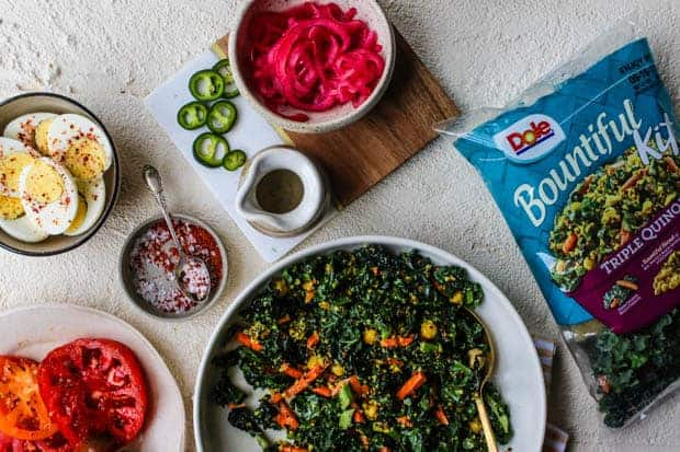 A bag of Dole Bountiful Kale and Quinoa salad is on a white table. there are small prep bowls scattered around the table each filled with a different colorful ingredient like sliced heirloom tomatoes, hard boiled egg halves sprinkled with red pepper flakes, slices of fresh green jalapeño, and a bowl of bright pink pickled onions.