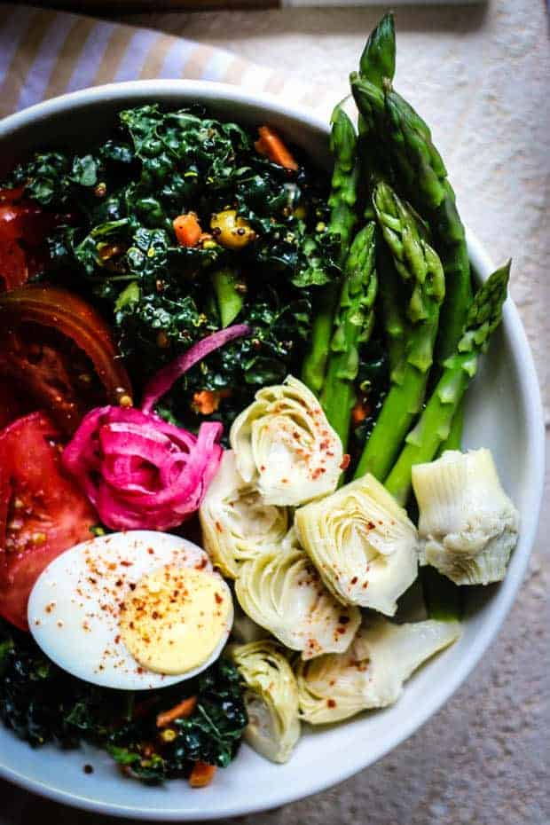 A close up of a bountiful bowl salad: a white bowl filled with kale and quinoa salad that has carrots and chickpeas tossed in. It has blanched asparagus spears, marinated artichoke halves, pink pickled onions, sliced heirloom tomatoes, and a hard boiled egg.