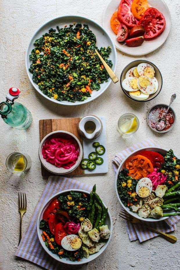 A really beautifu, colorful spread of food on a white table top. There are gigantic bowls of kale tossed with shredded carrots, quinoa, and chickpeas. Small bowls of ingredients like pink pickled onions, sliced heirloom tomatoes, and hard boiled egg halves. There are also 2 bowls of all of the ingredients assembled into a salad.