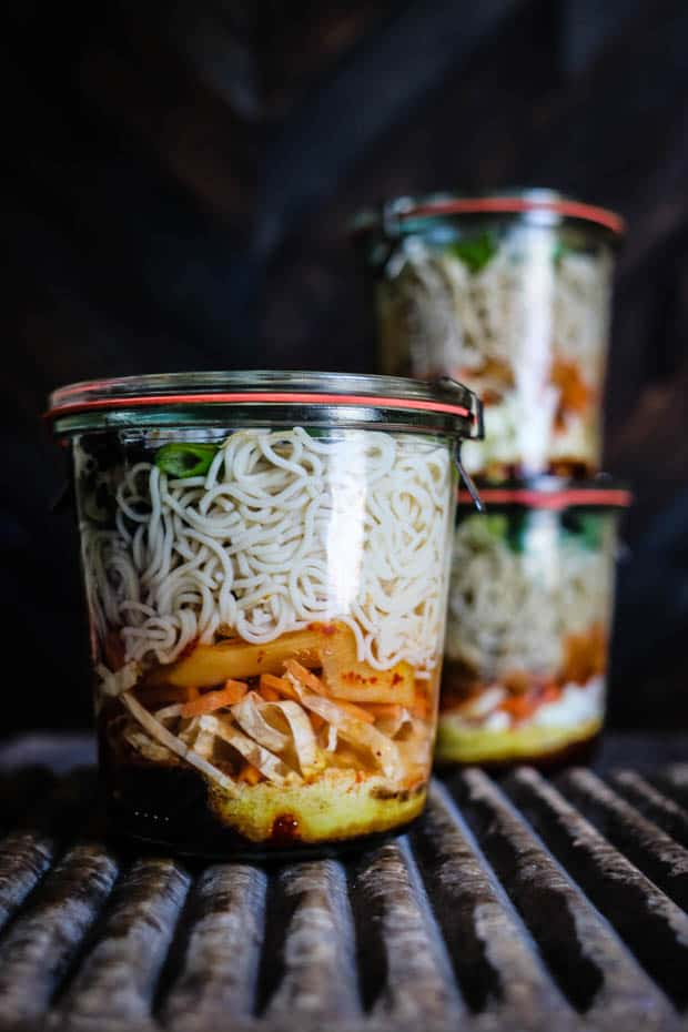 3 glass weck jars are on a wooden table top. The jars are layered with ramen ingredients - on the bottom is a yellow layer of spices and seasonings, then a layer of shredded green cabbage, shredded orange carrots, and red kimchi. Then the jars are layered with gluten free ramen noodles and green scallions.