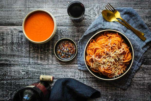 A dinner table scene with a bottle of wine and a bowl of pasta tossed in red sauce. There is a small bowl of red sauce on the table as well as a glass of red wine and silverware