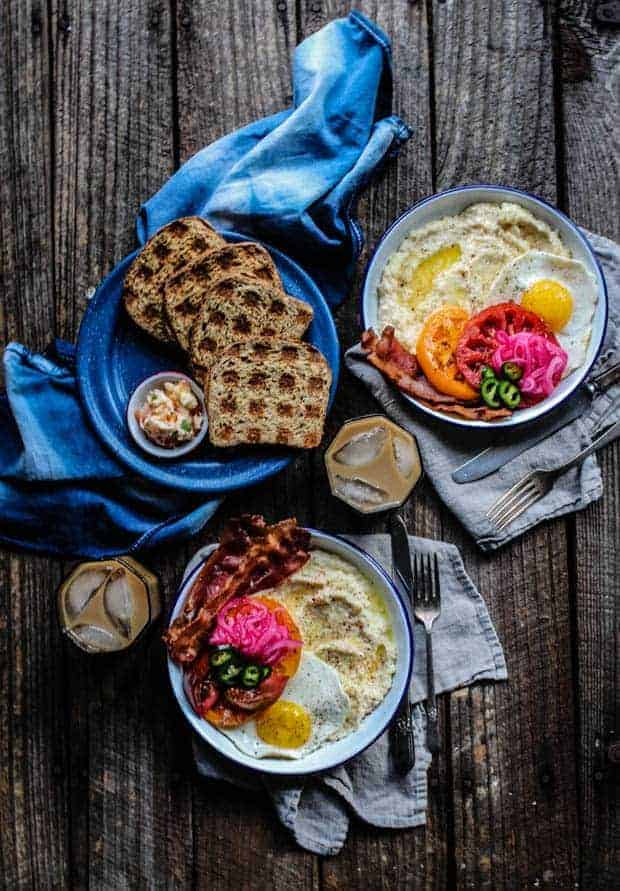 2 white and blue enamelware bowls are filled with cheddar cheese grits then topped with bacon, colorful slices of tomatoes, pink pickled onions, jalapeño slices, and a sunny side up egg. There is also a plate of toast that has been toasted in the waffle iron creating a grid pattern on the bread.