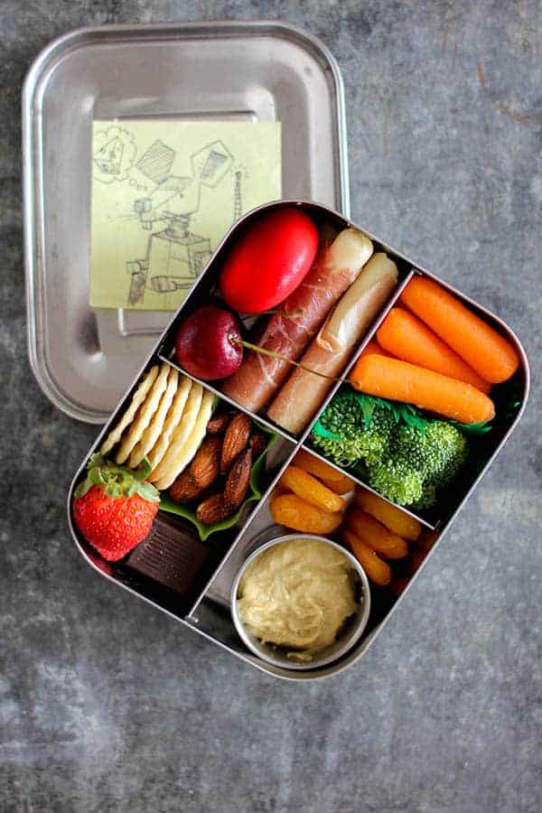 A stainless steel bento box with 4 compartments filled with a colorful assortment of meats, cheeses, crackers, fruits, and hummus.