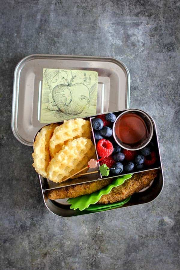 A bento lunchbox filled with toaster waffles, chicken strips a cup of maple syrup and fresh berries.