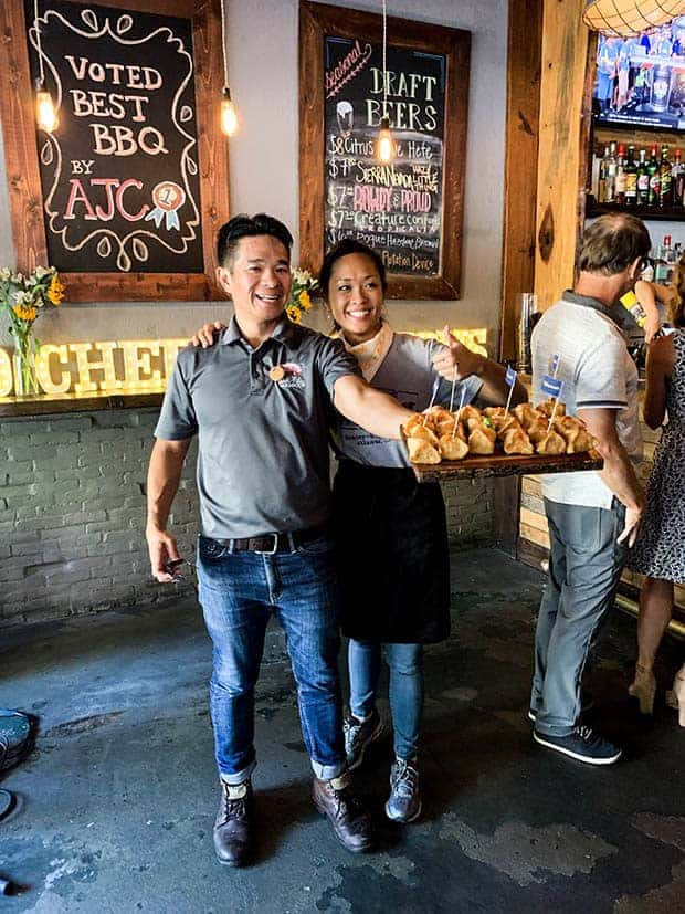 Chefs Howard and Anita Hsu of Sweet Auburn BBQ are standing in their restaurant. He is holding a wooden platter of pimento cheese wontons and she is giving the camera a thumbs up.