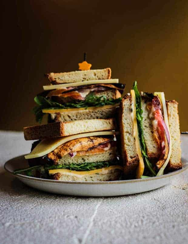3 halves of ultimate vegetarian club sandwich stacked on a plate.