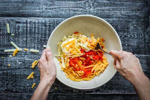 A mixing bowl with the ingredients for pimento cheese. A woman is stirring them together.