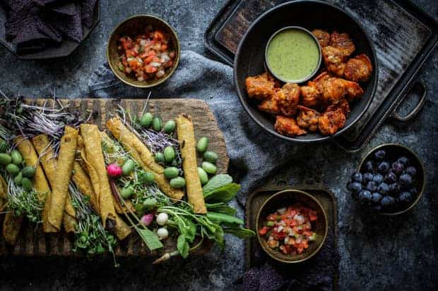 A Mexican inspired party spread. There is a large wooden board piled high with taquitos and fresh crudites. On either side of the table are heaping bowls of red salsa and a bowl of chorizo balls are off to the side as well.