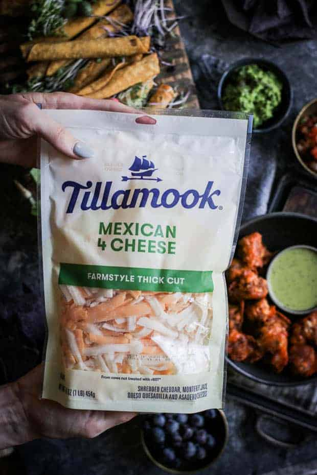A woman holding a bag of Tillamook Mexican 4-Cheese