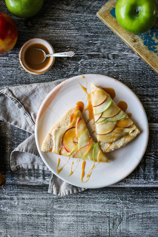 2 slices of easy apple desset pizza on a white plate - the slices have been drizzled with caramel. There are also green Granny Smith apples on the table.