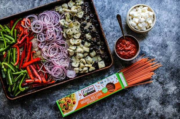 A sheet pan of roasted bell pepper strips, red onions, artichoke hearts, and black olives next to a box of Explore Cuisine red lentil pasta, a bowl of pizza sauce and a small bowl of mozzarella balls are on the table as well.