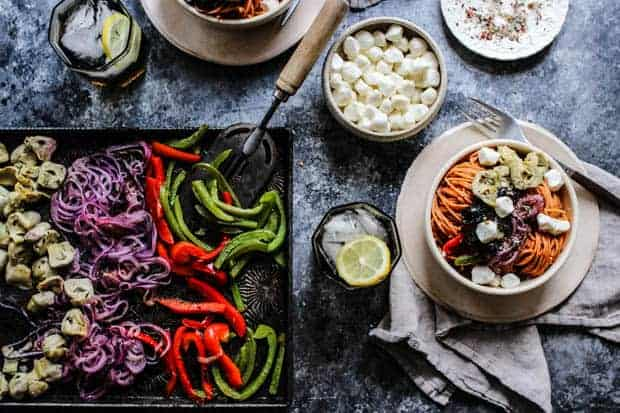 A sheet pan of roasted peppers and onions next to a bowl of red lentil pasta tossed with pizza sauce then topped with roasted vegetables like bell peppers, roasted onions, artichokes, and black olives. Topped with mozzarella balls.