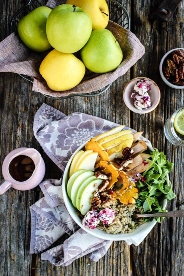 A giant, colorful buddha boiwl piled high with brown rice, arugula, fresh and pickled apples, fresh pears, roasted squash, and candied pecans.