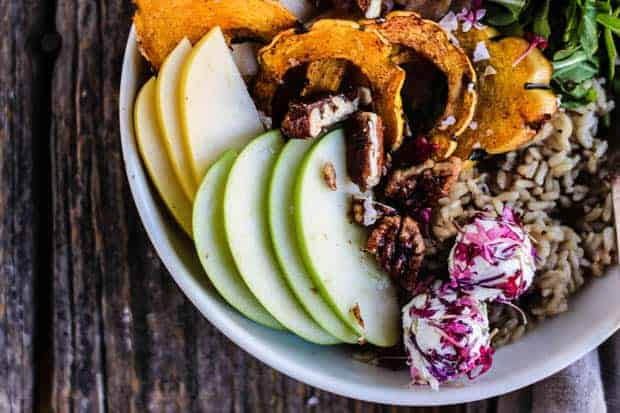 A close up picture of a Harvest Buddha Bowl with sliced apples, pears, roasted delicata squash, arugula, toasted pecans, and goat cheese.