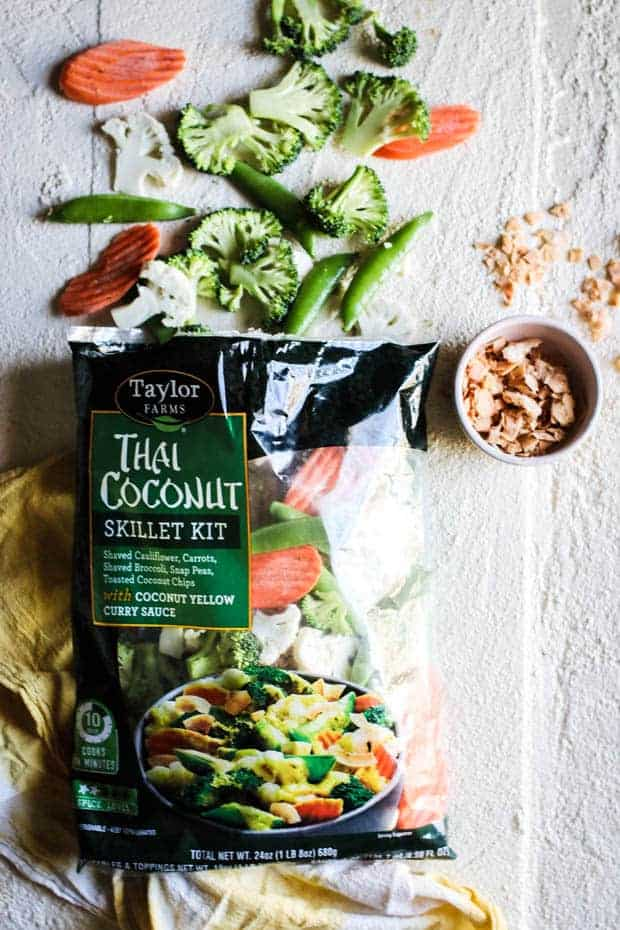 A bag of Taylor Farms Thai Coconut Curry stir fry kit with a bowl of toasted coconut next to it