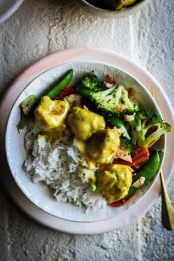 A bowl filled with jasmine rice then topped with stir fries broccoli, cauliflower, snow peas, and carrots. On top of the vegetables are 4 coconut curry meatballs smothered in yellow curry sauce