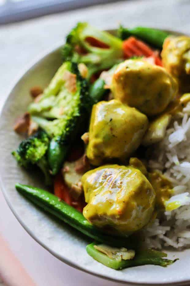 A bowl of Jasmine rice topped with stir fried cauliflower, broccoli, snow peas, and carrots then topped with Thai coconut curry meatballs