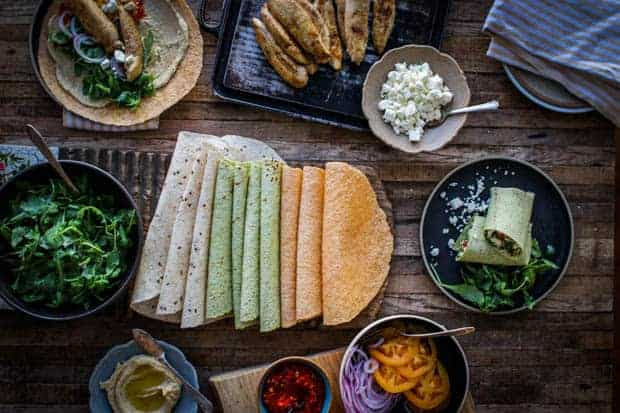 A platter of multi-colored wraps is in the middle of a table with a bowl of arugula. There are bowls of hummus, red pepper spread, brown butter chicken tenders, and feta cheese. There are 2 plate son teh table with wraps that have been preassembled.