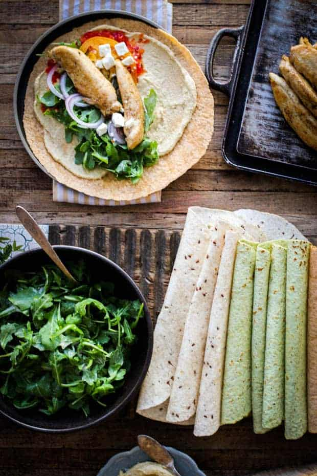 A table set with the fixings to make brown butter chicken wraps - there are bowls of arugula, hummus, and platters of chicken tenders. There are a variety of colored wraps. There is a wrap that has been built, waiting to be wrapped up.