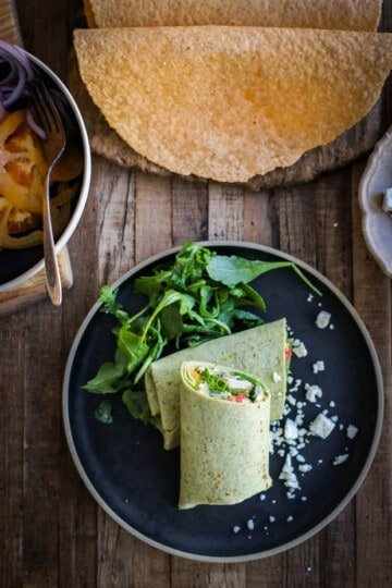 A brown butter chicken wrap on a black plate next to a platter of toufayan gluten free wraps. The wrap itself is spinach flavored so it is green and vibrant.