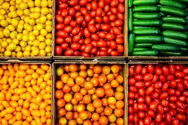 5 cartons of freshly picked yellow, red, and orange cherry tomatoes and a carton of small cucumbers all arranged side by side in color blocks.