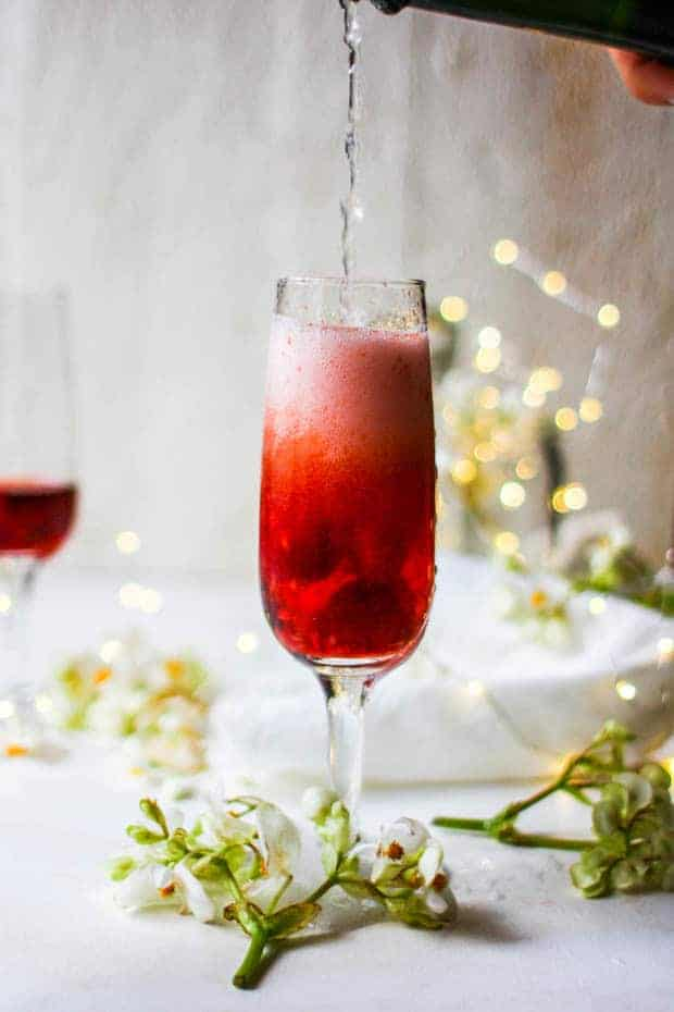 a wine glass is being filled with fizzy white wine. The glass has red aspberries and a red hied liquid in it already