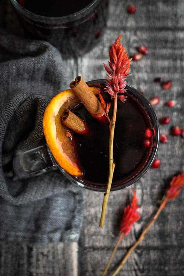 Lookin down into a mug of warm mulled red wine. There is a cinnamon stick, orange slice, and pomegranates floating in the mulled wine.