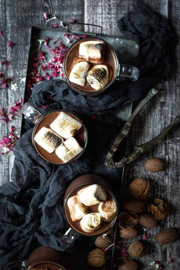 3 mugs of red wine hot chocolate are in a metal tray. Each mug is topped with toasted marshmallows. There is a dark colored cloth on the tray with the mugs of hot chocolate and there are walnuts in the shell, a vintage nut cracker an dpink flowers scattered all over the table.
