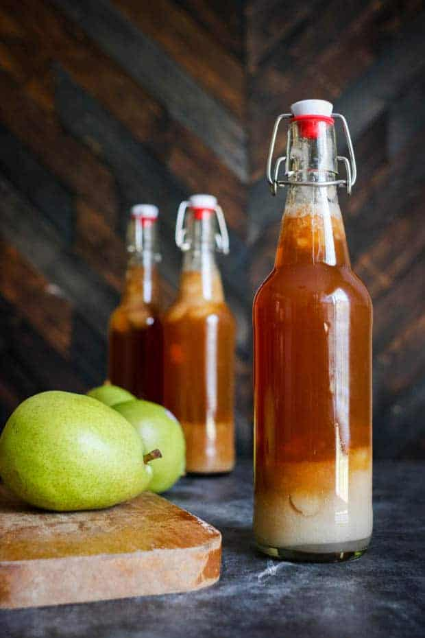 3 bottles of Chai Pear Kombucha on a table, one of the bottles is next to a green pear