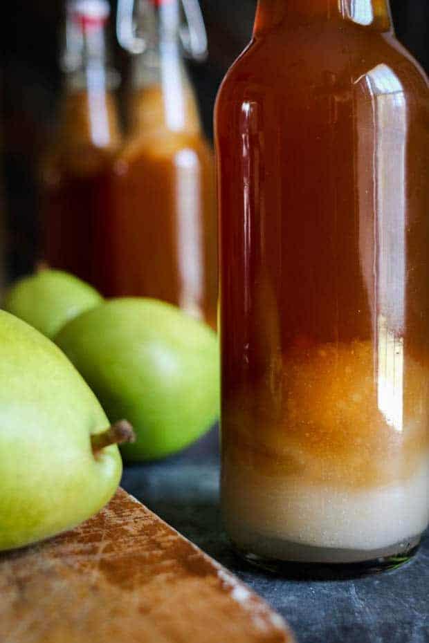 A closeup of a bottle of Chai Pear Kombucha next to a fresh green pear