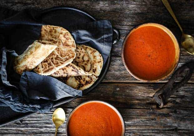 a basket with a gray linen napkin is full of golden paleo naan. There are two bowls of tomato soup next to the basket of naan bread.