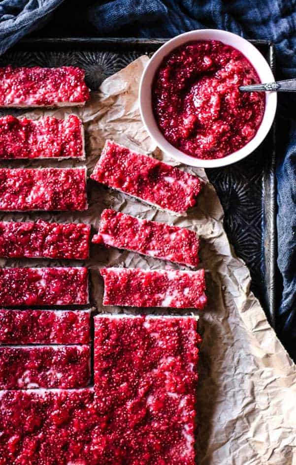 12 coconut bars layered with raw raspberry jam sit on a large piece of brow parchment paper. there is a sheet pan underneath the parchment and a bowl of raw raspberry jam next to the bars.