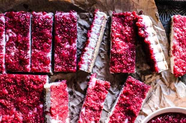 Close up of Paleo Raspberry coconut Bars turned different ways on a tray so you can see the crust, the white coconut filling, and teh red raspberry topping.