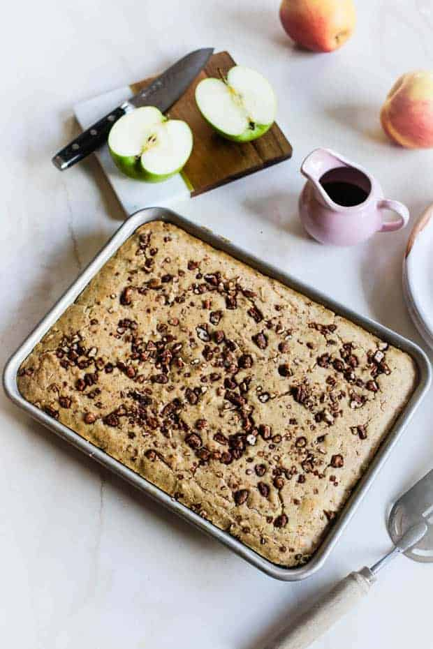 A sheet pan of apple sheet pan pancakes topped with candied pecans is on a table next to fresh slices apples on a cutting board and a small pitcher of maple syrup.