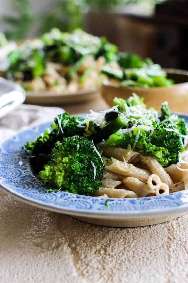 Big bowls of gluten free pasta tossed with lemon crea sauce and topped with blanched broccoli and asparagus.
