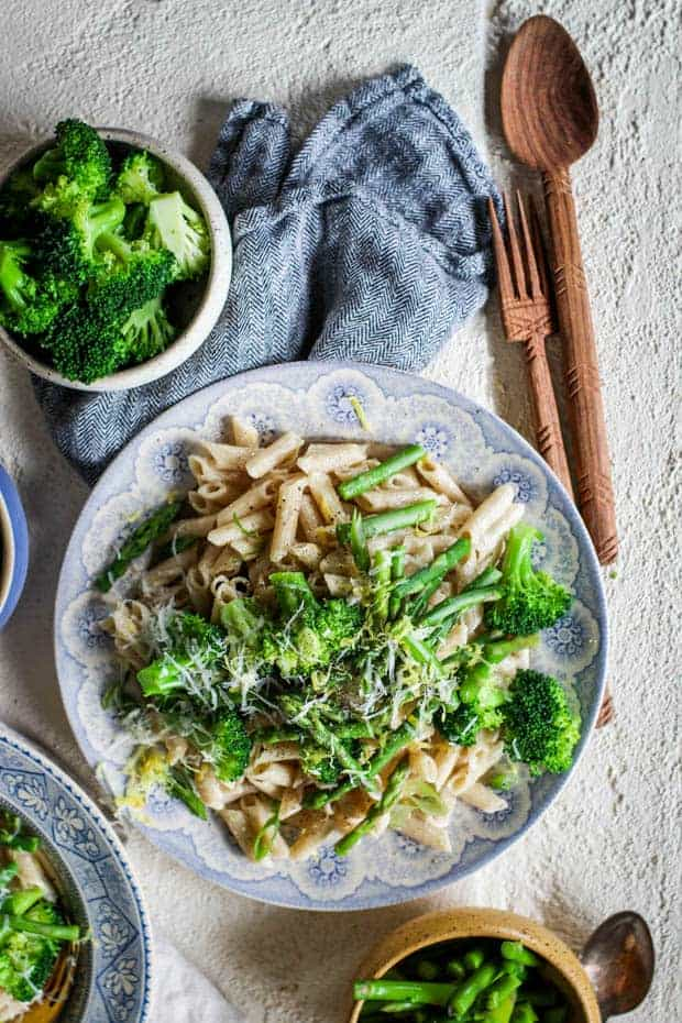 A ig bowl of lemon cream pasta with vibrant green veggies on top.