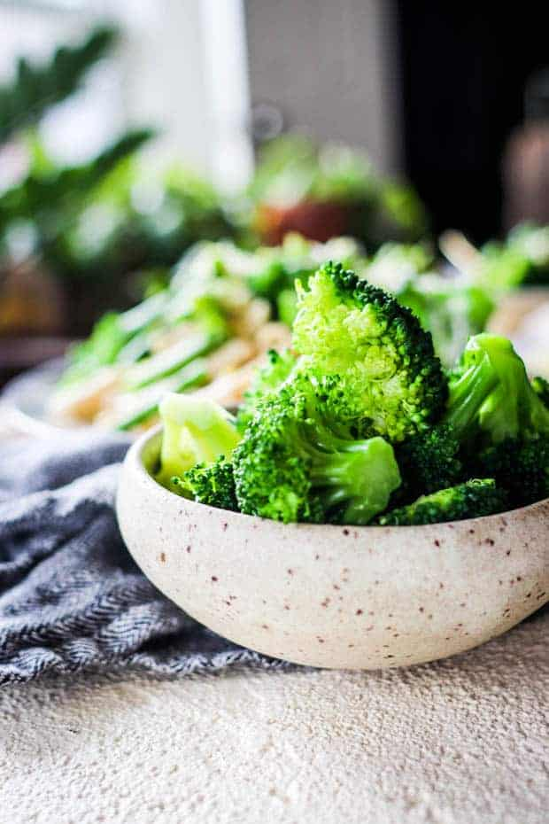 A bowl of vibrant green blanched broccoli