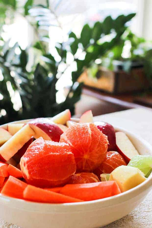 A bowl of citrus wit the peels removed, sliced apples, peeled ginger, chop-red carrots, and lime are on a table next to houseplants